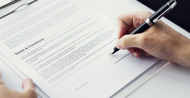 Closeup of hand signing paper workspace