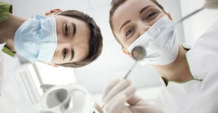 Skillful young female dentist is treating human teeth